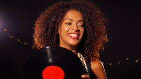 African-american young woman in party dress holding vinyl record and dancing on black lights background. Girl smiling. She is happy on New Year or Christmas