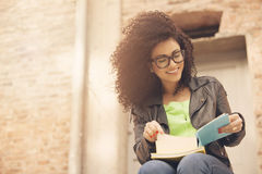 African american young woman reading with glasses. Happy african american woman reading book Royalty Free Stock Image