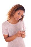 African American young woman sending a text message  Royalty Free Stock Images