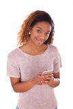 African American young woman sending a text message on her smartphone. Black teenager people Stock Images