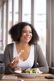 African american young woman sitting at cafe eating salad Stock Photography