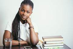 African young woman sitting at table with books at home. African american young woman sitting at table with books at home Stock Images