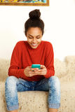 African american young woman using smart phone at home royalty free stock photography
