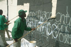 African-American youths painting over graffitti royalty free stock photography