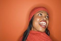 African-Americanfrau, die orange Schal und Hut trägt. Stockbild
