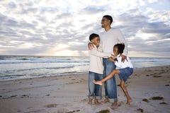 African-Americanvater und zwei Kinder auf Strand Stockfotos