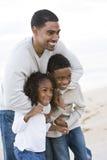 African-Americanvater und zwei Kinder auf Strand Stockfoto