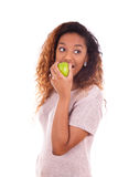 African Americanyoung woman eating one green apple - Black peopl Royalty Free Stock Images