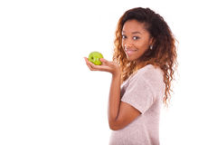 African Americanyoung woman holding one green apple. African American young woman holding one green apple Royalty Free Stock Photos