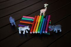 African animals with curiosity look at the multi-colored felt-tip pens royalty free stock photography