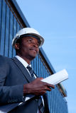 African architect holding building plans. Outdoor portrait of an African man with a hardhat and building plans Royalty Free Stock Photography