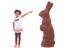 African Asian girl pointing a giant chocolate rabbit Stock Photography