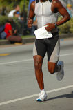 African athlete. Running black legs and body of a handsome African American athlete participating in an International Ironman triathlon competition Royalty Free Stock Images