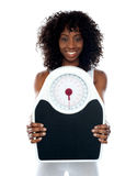 African athlete showing weighing scale Royalty Free Stock Photo
