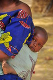 African baby carried on the back. African baby carried by mother on the back, traditional way  in hausa village Niger, West Africa Royalty Free Stock Photo