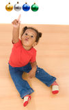 African baby girl pointing four balls of Christmas. Sitting on wooden floor royalty free stock images