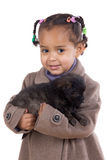 African baby holding a puppy on her arms. Isolated over white royalty free stock image