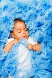 African baby laying and sleeping on the blue cloth. Chubby African small baby laying and sleeping on the blue cloth close-up view royalty free stock photography