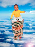 African baby sitting on stack of books Stock Image