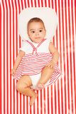 African baby in striped dress laying on blanket Stock Image