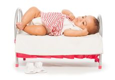 African baby in striped dress on the small bed royalty free stock photo