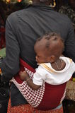 African baby. An African woman carries her babe using the typical African way with a cotton sheet Royalty Free Stock Image