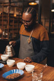 African barista pouring coffee in a modern roastery Royalty Free Stock Photography