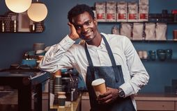 African barista smiling at camera relaxing after workday with coffee while leaning on the counter at coffee shop. royalty free stock photos