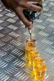 African Barman hand pouring a round of shots stock images