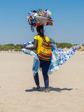 African beach vendor. An African woman working as beach vendor on a beach in Ugento, south Italy
