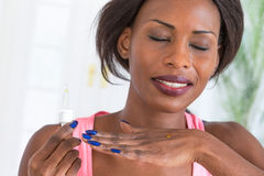 African beauty. Beautiful African woman using essantial oil for well beiing Stock Image