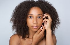African beauty woman with curly hair. Close up portrait of an african beauty woman with curly hair posing with hands by face stock photo