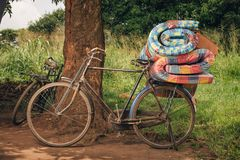 African bike with rolled beds on the back lays against a tree, ready to be ridden back to the nearby village. Based in Uganda, Africa stock photography