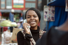 African or black American woman calling on landline telephone. African or black American woman calling on landline payphone telephone in Alexandra township Royalty Free Stock Photography