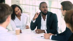 African businessman talking handshaking colleague at group meeting negotiations