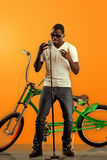 African black man singing at microphone with a bicycle in back on orange background Stock Photo
