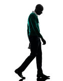 African black man walking looking down sad silhouette. One african  black man walking looking down sad  in silhouette studio on white background Stock Photography