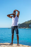 African black man wearing white vest and blue short jeans. Standing African black man wearing white vest and blue short jeans. Male model thinking while alone by Royalty Free Stock Photo