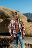 African black model with six pack in unbuttoned checkered shirt. African black man model with six pack in unbuttoned checkered shirt,  against a beach rocks Royalty Free Stock Image