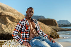 African black model with six pack in unbuttoned checkered shirt. African black man model with six pack in unbuttoned checkered shirt,  against a beach rocks Stock Photo