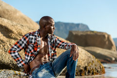 African black model with six pack in unbuttoned checkered shirt. African black man model with six pack in unbuttoned checkered shirt,  against a beach rocks Royalty Free Stock Photography