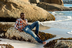 African black model with six pack in unbuttoned checkered shirt. African black man model with six pack in unbuttoned checkered shirt,  against a beach rocks Stock Images