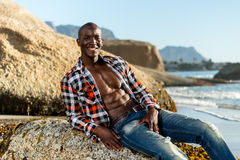 African black model with six pack in unbuttoned checkered shirt. African black man model with six pack in unbuttoned checkered shirt,  against a beach rocks Stock Photography