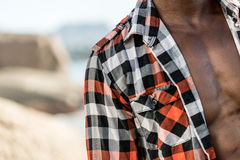 African black model with six pack in unbuttoned checkered shirt. African black man model with six pack in unbuttoned checkered shirt, isolated against a beach Royalty Free Stock Photography
