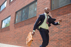 African black young businessman running in a city Stock Photos