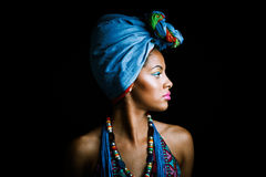 African black young woman beauty portrait with turban studio. African black young woman beauty portrait with turban headscarf and traditional colorful clothes Royalty Free Stock Photos