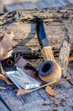 African block Meerschaum pipe outdoors. African block Meerschaum smoking pipe with a fumed rim, rests against a rustic log outdoors Stock Image