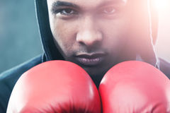 African boxer. Close up of African American boxer wearing red gloves and black hoodie and standing against gray background. Concept of sports career Stock Photos