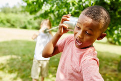 African boy calling friend with tin can telephone. In summer in the park Stock Images