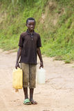 African boy carring water Stock Photos